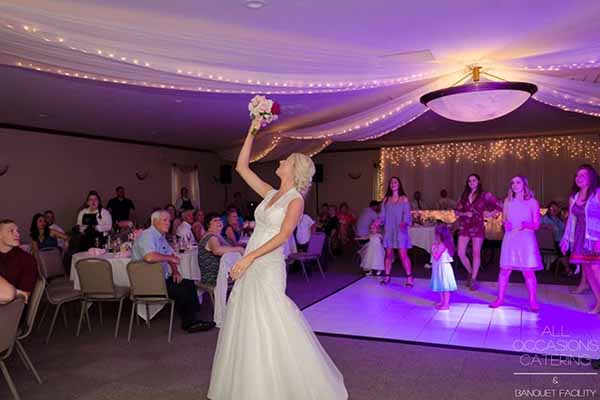 A bride tosses her bouquet at a country themed wedding
